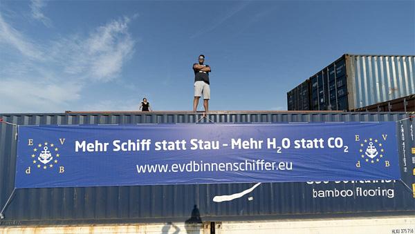 Containerschiff mit Banner des evdb-Slogan